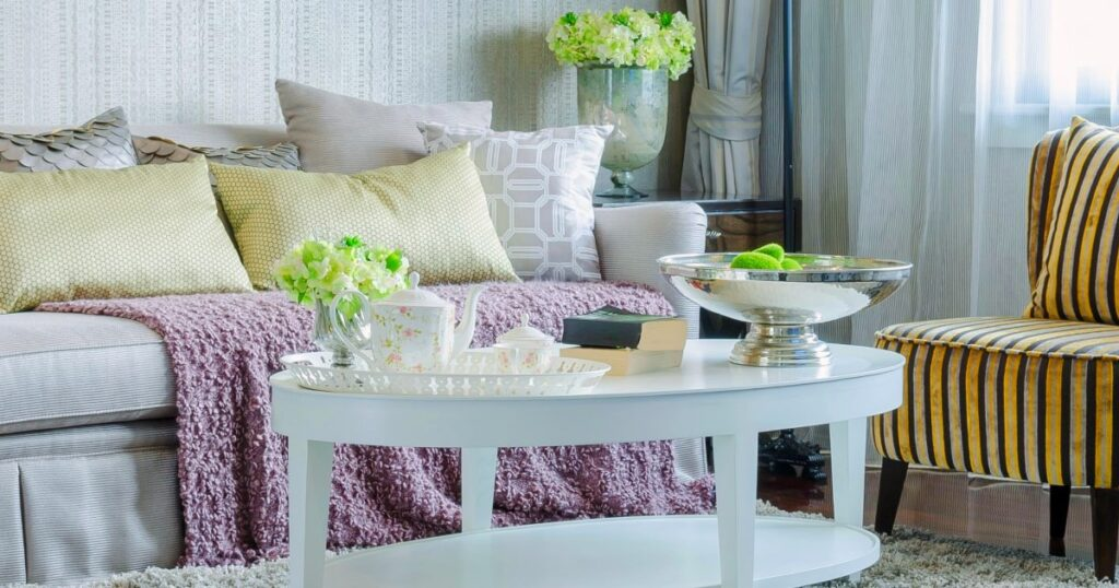 Small living room decorated with white couch and table with pillows and flowers