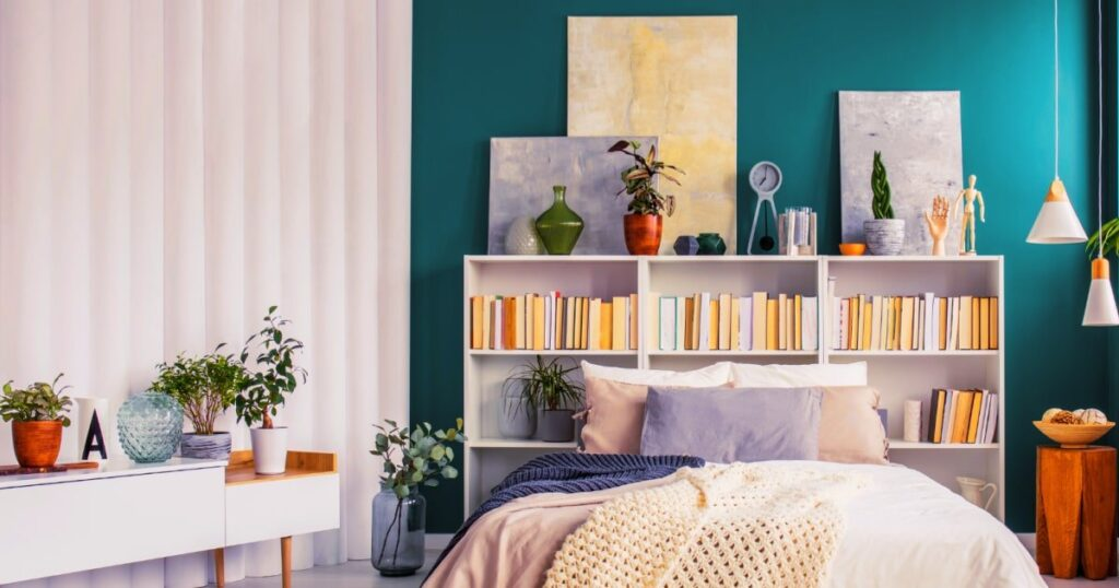 A small bedroom idea to save space is put bookcases behind the bed and store books and decor on them