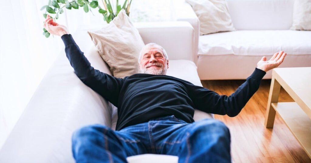 dad who says he wants no gifts laying on couch arms outstretched