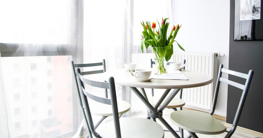 simple white dining table and chairs in small black and white dining room